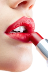 Extreme close up on gorgeous model applying red lipstick